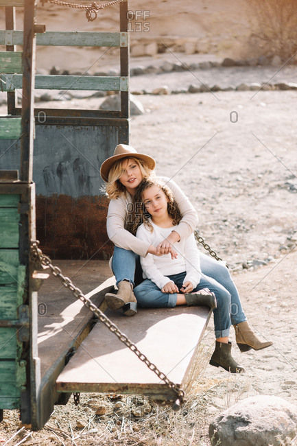 Content woman with blonde hair in hat cuddling daughter in casual clothes while having rest and sitting in old truck body
