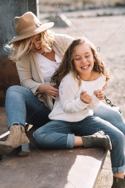 Content woman with blonde hair in hat cuddling and tickling daughter in casual clothes while having rest and sitting in old truck body