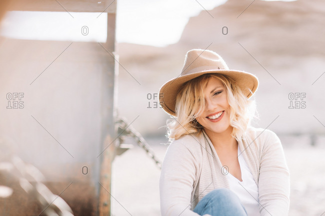 Smiling female in hat with blonde hair dressed in bright casual clothes looking at camera sitting near truck body in village at daytime