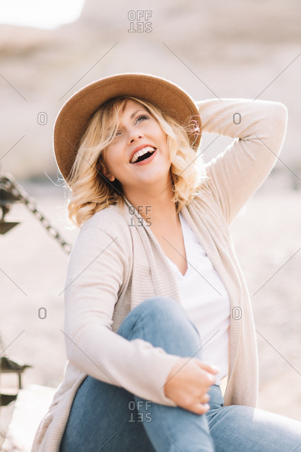 Smiling female in hat with blonde hair dressed in bright casual clothes looking away sitting near truck body in village at daytime