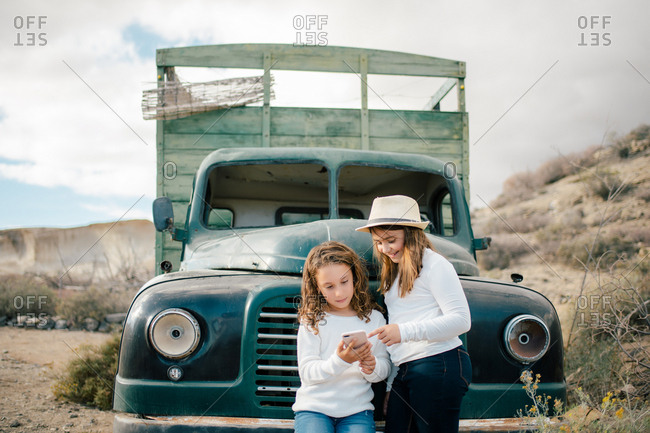 Laughing children in white jumpers and jeans sharing mobile phone watching video while leaning on vintage dark green truck