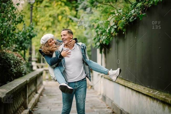 Content woman in casual clothing sitting on back and kissing pleased man walking on small alley with green plants on blurred background