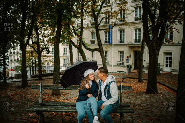 Content woman in casual clothing sitting with young man on bench of beautiful neighborhood holding an umbrella