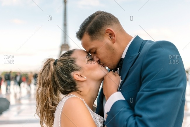 Groom in blue suit and bride in white wedding gown kissing passionately with Eiffel Tower on background at Paris