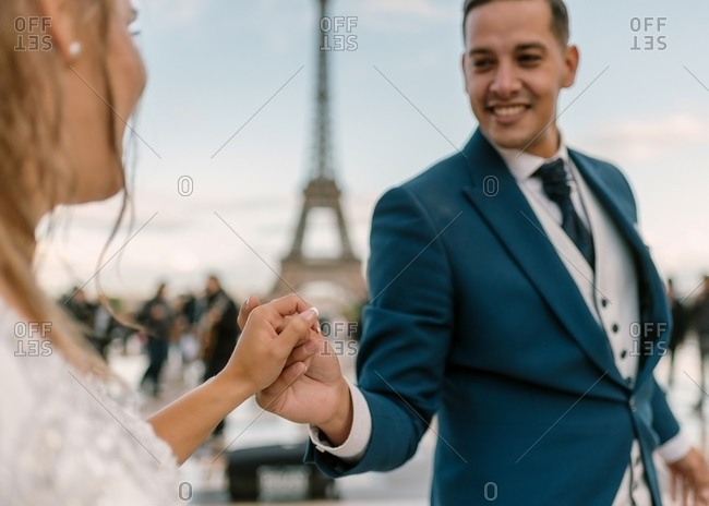 Groom in blue suit and bride in white wedding gown having slow dance smiling and looking at each other with Eiffel Tower on background at Paris