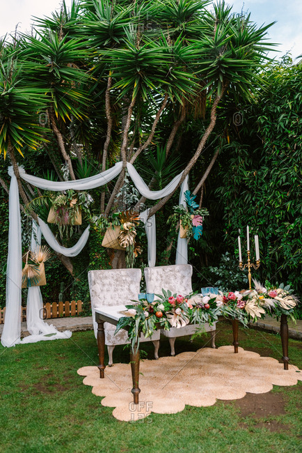 Set for wedding ceremony with newlyweds table decorated with flowers arrangement and placed on carpet against green tropical tree with white wedding arch