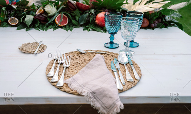 White wooden table without cloth decorated with fruit and flowers arrangement and served with cutlery and linen napkin on wicker napkins and blue glasses