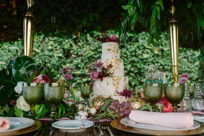 White and gold tiered cake with flowers placed on wedding table with plate and glasses decorated with fruits and flowers against green trees