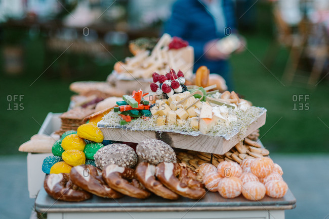 Wooden tray with canapes placed on tray with cookies and fruits in candy bar served during wedding ceremony outdoors