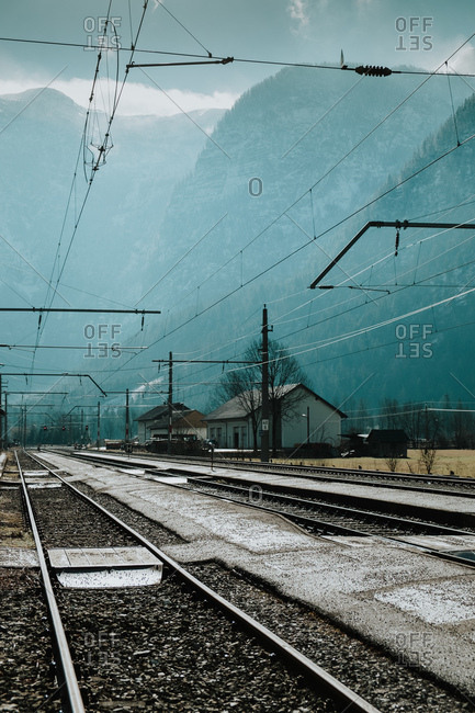 Empty railway and electric wires passing through mountains drowning in foggy haze in Hallstatt