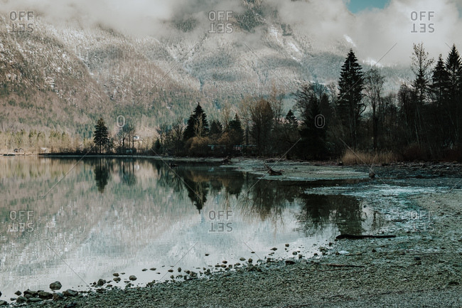 Picturesque landscape of calm transparent lake surrounded by snowy mountains and dark forest in Hallstatt