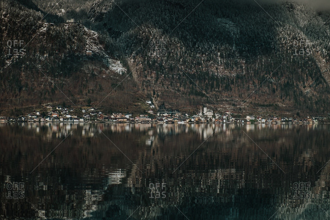 Dramatic landscape of transparent lake surrounded by dark mountain with tree in Hallstatt