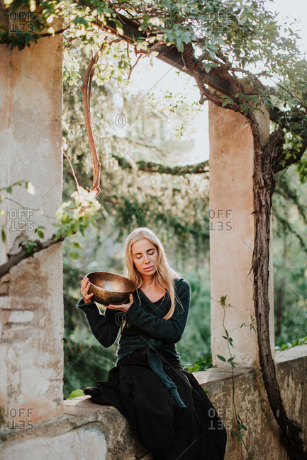 Charming blonde female in long gown clothes with closed eyes and holding metal musical bowl while sitting in ruins of old castle in historic place