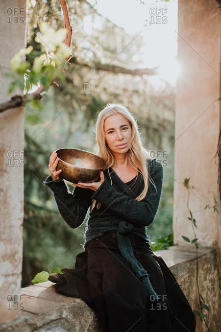 Charming blonde female in long gown clothes looking at camera and holding metal musical bowl while sitting in ruins of old castle in historic place