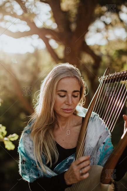 Romantic charming woman with blonde hair enjoying melody while playing musical instrument and sitting in garden in summer sunny day