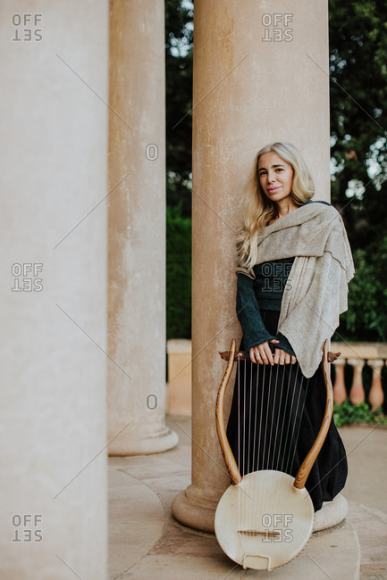 Romantic attractive blonde female musician in casual clothes resting after performance and holding wooden lyre while leaning on pillar at building entrance