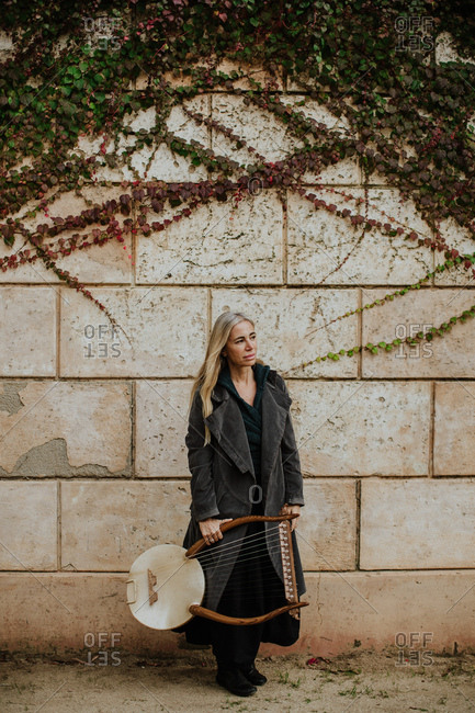 Thoughtful charming blonde female musician in coat holding string musical instrument while standing at old stone wall in autumn day