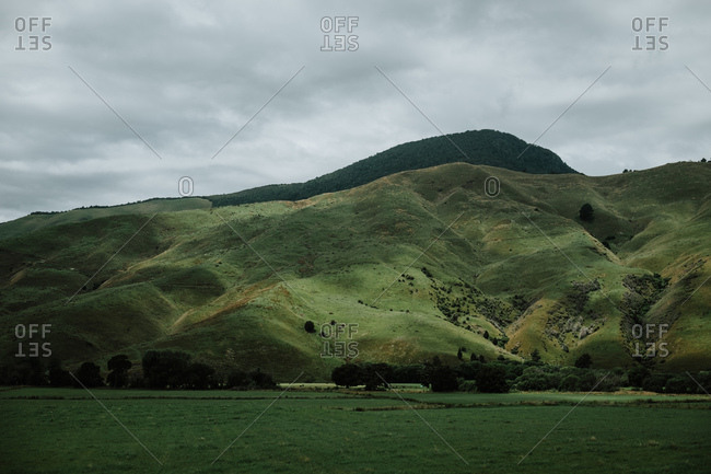 Scenic landscape of flat green field and mountain hills covered with green grass against grey cloudy sky at New Zealand countryside