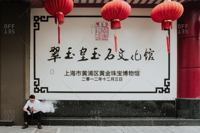 Shanghai, China - 12 December, 2018: Young man in formal wear smoking and using mobile phone while sitting next to  building with big signboard and red Chinese lanterns
