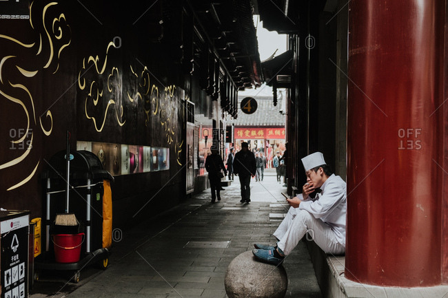 Shanghai, China - 12 December, 2018: Side view of young male in white uniform smoking and using smartphone while sitting next to building on narrow pedestrian street