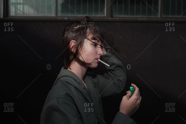 Side view of rebel young brunette in stylish casual jacket with blue nails lighting up cigarette at city street