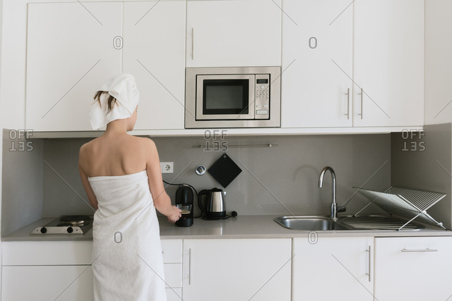 Back view of relaxed female in white bath towels preparing beverage using coffee machine standing in modern comfortable kitchen with white furniture set and built in appliance in apartment in loft style