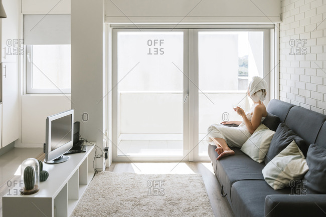 Adult relaxed woman enjoying life while resting on sofa and having hot drink after shower in own cozy apartment