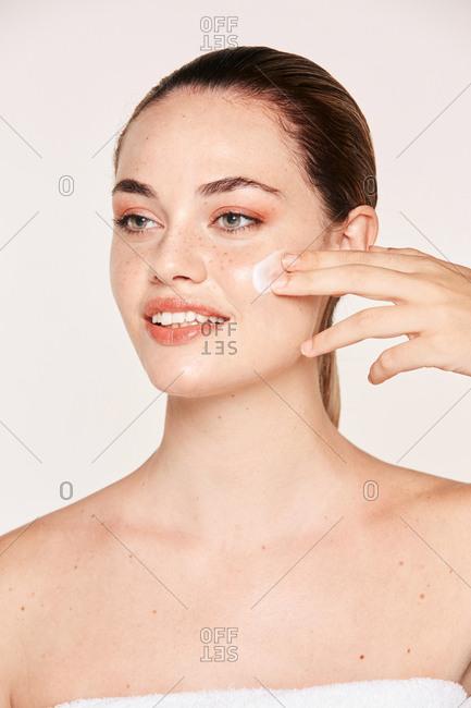 Amiable female taking care of face