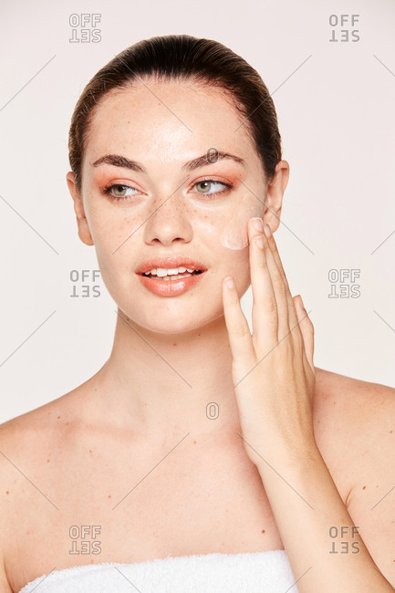 Graceful woman with pure skin applying cream while posing and looking away isolated on white background