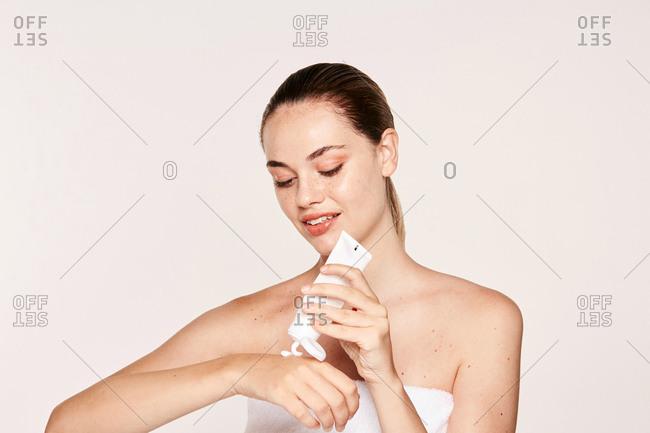 Appealing female applying moisturizing cream on hands