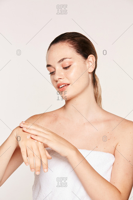 Pretty woman in towel creaming hand with moisturizing gel isolated on white background