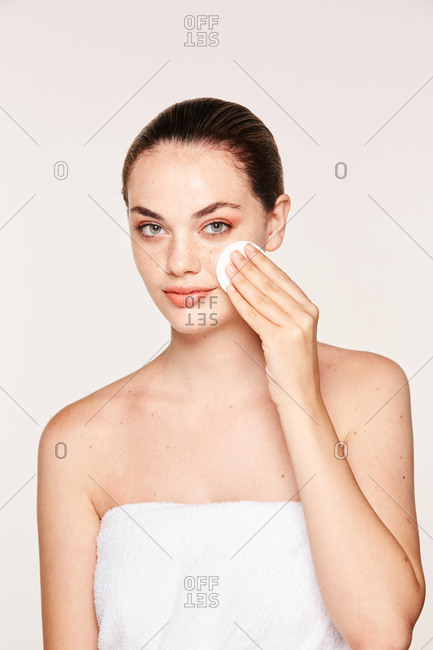 Peaceful female applying toner on radiant face with sponge