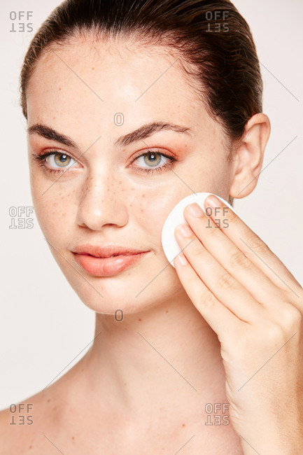 Freckled woman cleansing face skin face with lotion on cotton sponge isolated on white background
