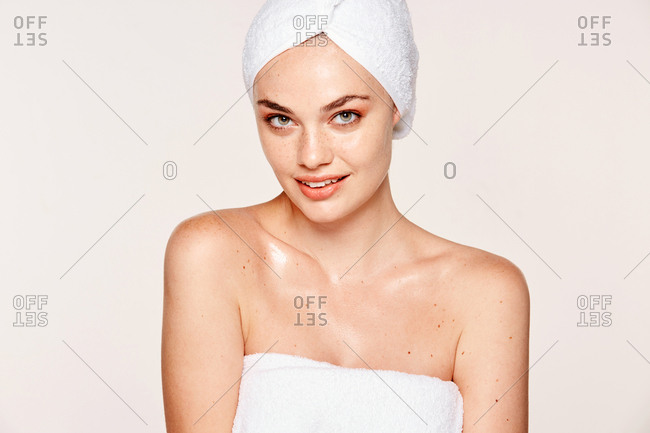 Good-looking woman with moisturized skin posing in towel on face and body isolated on white background