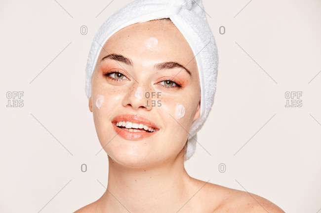 Delighted female with radiant skin applying cream