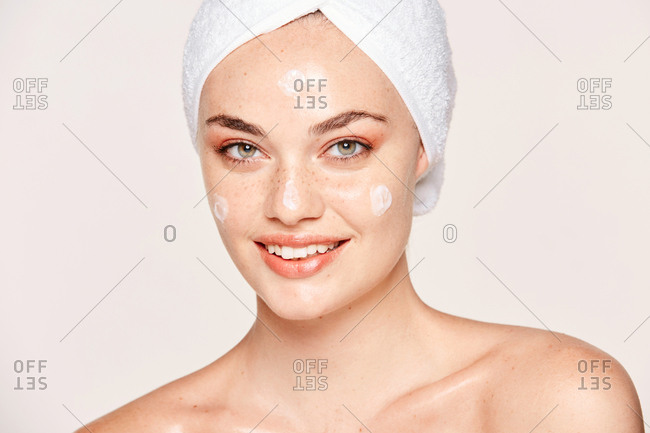 Positive freckled woman with towel on head and healthy skin taking care of face with cream and looking at camera isolated on white background