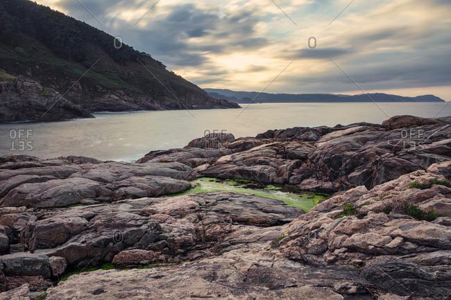 Foggy surface of sea with big rocks on sandy beach and mountains on sunrise at Portonovo beach at Italy