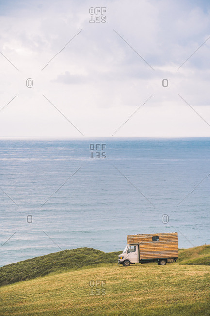 Golden field on hill and small cargo truck with blue sea and cloudy sky on background at Comillas Cantabria at Spain