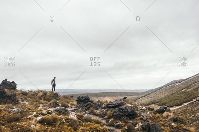 Traveler enjoying in views at rocky terrain with cloudy sky on background at New Zealand
