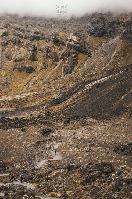 December 21, 2017: From above of colorful big rocky terrain with tourists trekking at Tongario of New Zealand