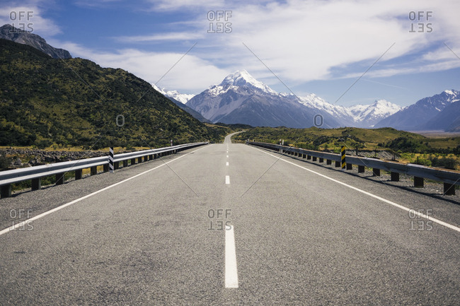 Asphalt road amid tropical green cliffs with cloudy blue sky and mountain Cook with snow on top on the background