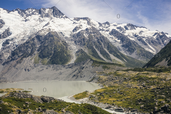 Powerful overgrown cliffs near small lake and big snowy mountain Cook with blue skyline on background at Ne Zealand