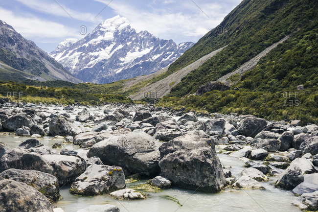 Rocky river among green cliffs with mountain Cook and heaven on background at New Zealand