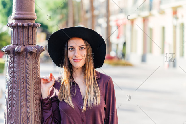 Confident long haired female in stylish purple blouse and black hat standing next to pile and looking at camera with city street on blurred background