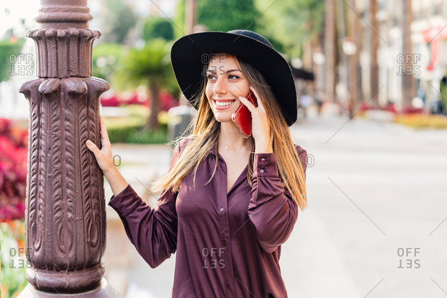 Content long haired lady in fashionable black hat and shirt walking on the street while calling on mobile phone and looking away at city street