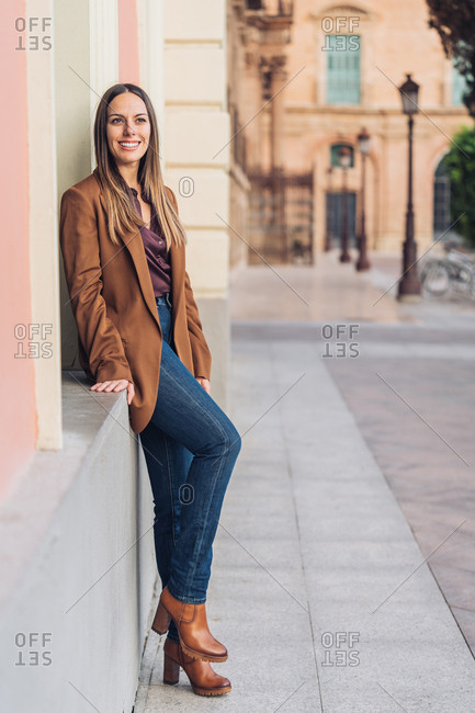 Satisfied charming lady in stylish casual clothing and heels leaning on wall of building and looking away at city street