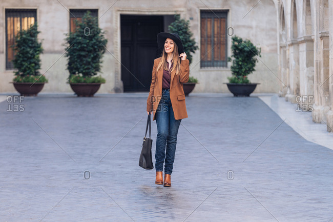 Excited female in stylish casual wear and black hat walking and looking away on sidewalk among old buildings