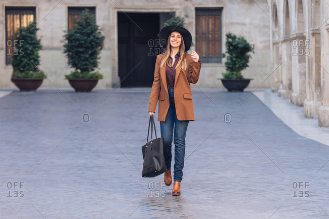 Excited female in stylish casual wear and black hat walking and looking at camera on sidewalk among old buildings