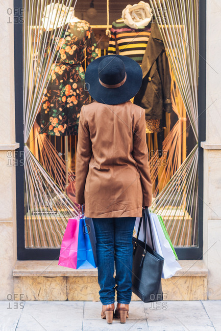 Back view of unrecognizable lady in stylish hat and brown jacket looking through shop window on fashionable dress with roses at city street