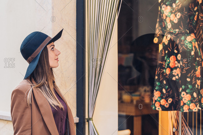 Side view of young lady in stylish hat and brown jacket looking through shop window on fashionable dress with roses at city street